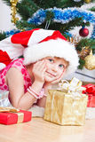Girl with gifts near a New Year tree Stock Image