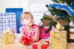 Girl with gifts near a New Year tree Royalty Free Stock Images