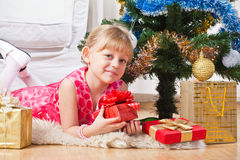 Girl with gifts near a New Year tree. Soon new year! Little girl at a Christmas fir-tree royalty free stock image