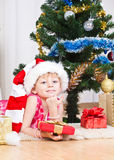 Girl with gifts near a New Year tree. Soon new year! Little girl at a Christmas fir-tree stock photo