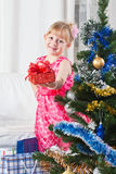 Girl with gifts near a New Year tree. Soon new year! Little girl at a Christmas fir-tree royalty free stock photo