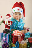 The girl with gifts by new year. The girl in a red cap with multi-coloured gifts and Sant? to Christmas and new year Royalty Free Stock Images