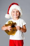 Girl with gifts in santa hat Royalty Free Stock Photos
