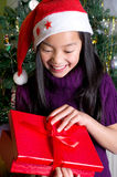 Girl with gifts under the Christmas tree Stock Images