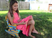 Girl Giggles Over Pink Dress While Sitting in Rocker royalty free stock photos