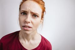 Girl with ginger hair and freckles, looking in camera with angry expression. Unhappy handsome girl with ginger hair and freckles, looking in camera with angry Royalty Free Stock Photography