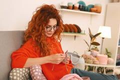 Girl with ginger hair wearing glasses knitting baby clothes. Baby clothes. Appealing girl with ginger hair wearing glasses feeling enthusiastic while knitting royalty free stock image
