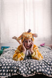 Girl in giraffe onesie on her bed Royalty Free Stock Photography