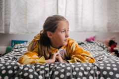 Girl in giraffe onesie on her bed Royalty Free Stock Images