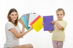 Girl and girl are holding colorful monochrome images Stock Photos