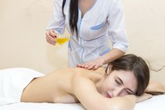 The girl is given a therapeutic massage with bee honey. In the clinic Royalty Free Stock Photography