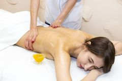 The girl is given a therapeutic massage with bee honey. In the clinic Stock Images