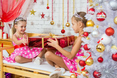 Girl gives a big red Christmas gift another girl sitting on the bench Stock Photos