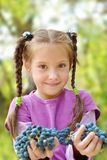 Girl gives bunches grapes Stock Images