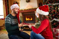 Girl gives Christmas gift to boyfriend Royalty Free Stock Photo
