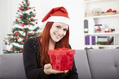Girl gives christmas present to someone Royalty Free Stock Image