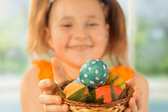 Girl gives Easter basket with eggs Stock Photos