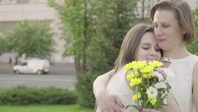 The girl gives flowers. A beautiful daughter gives flowers to her mother.  stock video footage