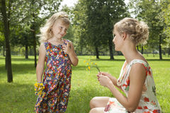 Girl gives a flowers mother Royalty Free Stock Image