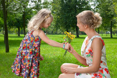 Girl gives a flowers to her mother Stock Photo