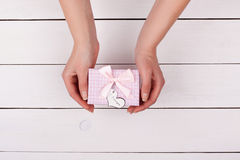 Girl gives a gift. Female hand holding a gift with a bow. Above the table Royalty Free Stock Photography