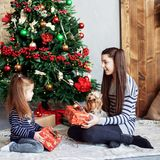 Girl gives gift to sister. The concept of Christmas and New Year royalty free stock photos
