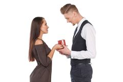 A girl gives her boyfriend a gift box, the guy takes a present. Valentine`s Day. Isolated. Royalty Free Stock Photos