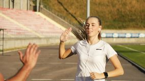 Girl Gives High Five to Trainer. Slender girl giving high five to well-built trainer as jogging in the stadium stock footage