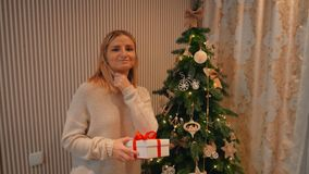 The girl gives his girlfriend a New Year gift under the tree. A young blond girl in a white woolen sweater gives a New Year`s gift to her best friend near a stock footage
