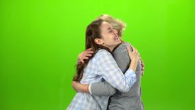 Girl gives the keys to her mom. Green screen. Side view. Woman gives the keys to her daughter, she embraces and kisses mom. Green screen. Side view stock video footage
