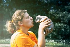 the girl almost gives a kiss to the puppy. on hands. there is toning stock images