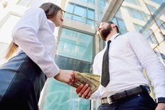 A girl gives a man in the hands of money in the background of an office building. Payment for services. Salary in the envelope. royalty free stock photography