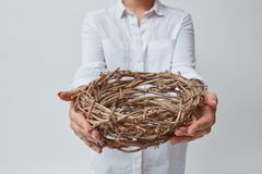 Girl gives a nest of twigs. Isolated on a gray background. Easter royalty free stock photos