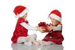 The girl gives to the sister a gift. Royalty Free Stock Photo