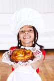 Girl giving an apple pie. Smiling african american girl in apron and hat giving an apple pie royalty free stock images