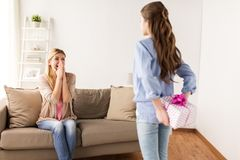 Girl giving birthday present to mother at home. People, holidays and family concept - happy girl giving birthday present to mother at home Royalty Free Stock Image