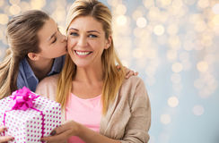 Girl giving birthday present to mother over lights. People, holidays and family concept - happy girl giving birthday present to mother over lights background Royalty Free Stock Photos