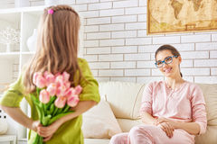 Girl giving a bouquet to mother Stock Photos