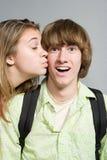 Girl giving boy a kiss on the cheek Royalty Free Stock Photos