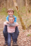 Girl Giving Boy Piggyback Ride On Countryside Walk Stock Photo