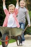 Girl Giving Boy Ride In Wheelbarrow Stock Image
