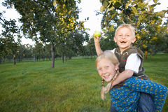 Girl (11-13) giving brother (9-11) piggy back, boy with apple, smiling, portrait stock image