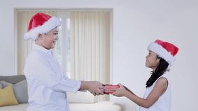 Girl giving Christmas gift to her brother at home. Cute little girl giving a Christmas gift to her brother at home while wearing Santa hat stock video