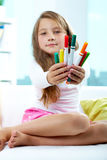 Girl giving crayons Stock Image