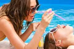 Girl giving a drink to the other on the pool Royalty Free Stock Images
