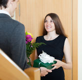 Girl giving flowers and gift. Beautiful women giving flowers and gift to men at home door stock photo