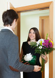 Girl giving flowers and gift. Pretty girl giving flowers and gift to guy at home door royalty free stock photos