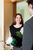 Girl giving flowers and gift to man. Girl giving flowers and gift to men at home door stock photography