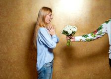 Girl giving flowers in the studio on a gold background, the conc. Ept of St. Valentine`s Day Stock Images