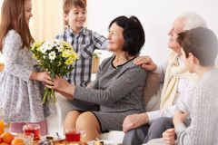 Girl giving flowers to her grandma Stock Images